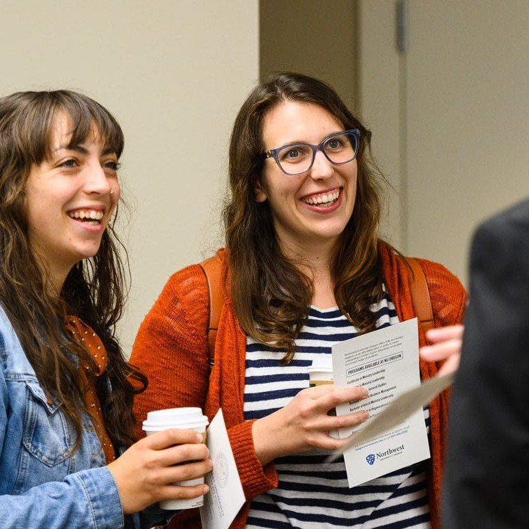 Two female students talking with a professor between classes holding cups of coffee.